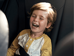 Little boy laughing in car