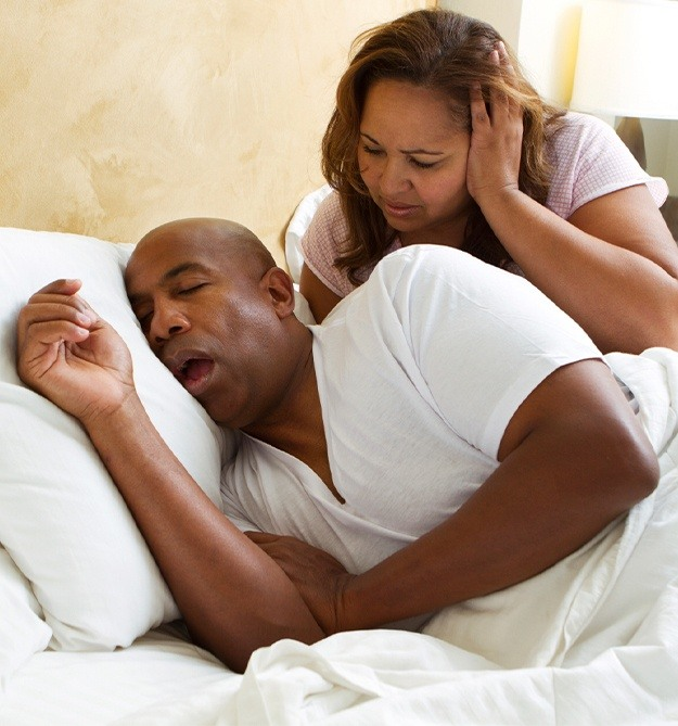 Woman frustrated in bed next to snoring man