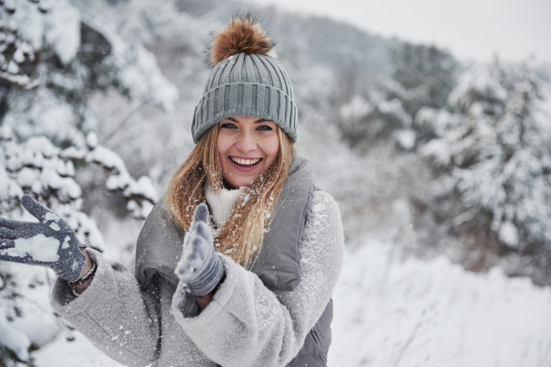 a woman smiling while out in the snow
