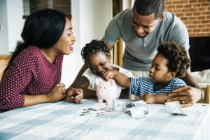 family sitting at a table and placing money in a piggy bank