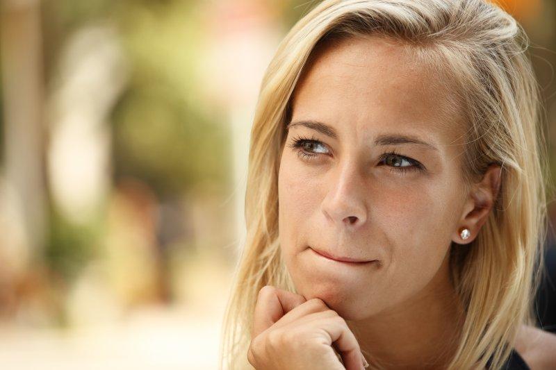 woman blonde hair pondering dental tips from her dentist