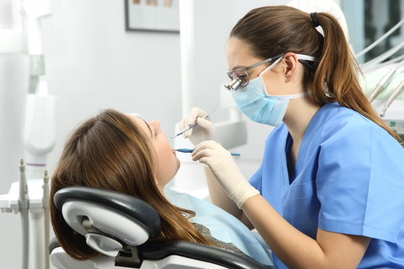 Dental hygienist examining patient's teeth