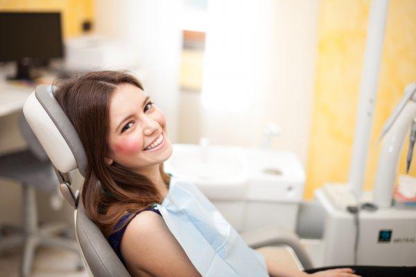 A woman smiling at her dental checkup.