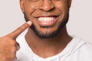 close-up of a man pointing to his smile