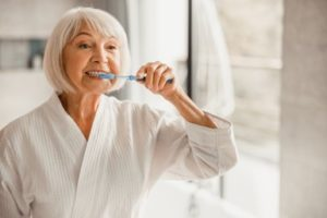 Mature woman with white hair wearing a white bathrobe brushing her teeth with a blue toothbrush